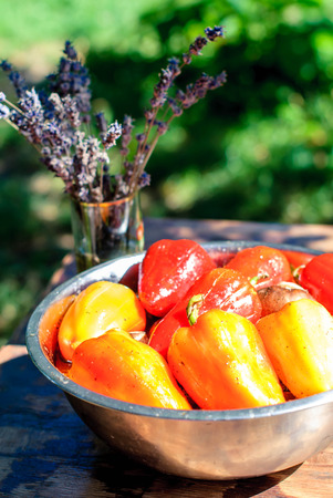 Red and yellow salad peppers in marinade for grilling and a bouquet of lavender on the summer table Stock Photo