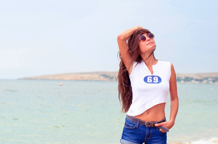 short shorts: Beautiful young girl with long hair wearing round glasses and a short T-shirt on the beach.