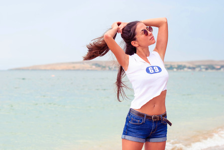 Beautiful young girl with long hair wearing round glasses and a short T-shirt on the beach.
