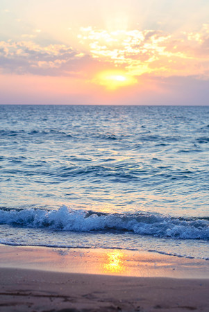 Sunset on the calm sea and sandy beach for the background.