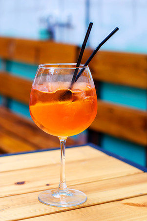 spritz: glass of aperol spritz cocktail on a wooden table