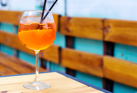 glass of aperol spritz cocktail on a wooden table