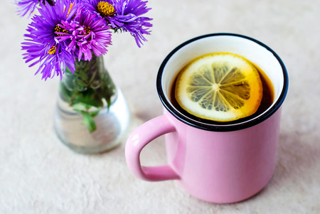 A pink mug with black tea and lemon and a glass vase with flowers. Stock Photo