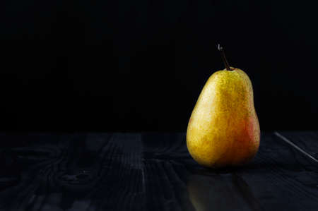 Just a yellow pear on a black background and a wooden table Stock Photo