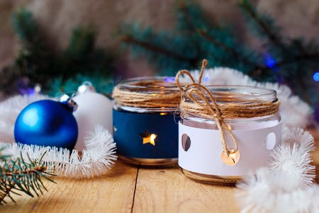 Christmas candles with Christmas tree decorations, white and blue and Christmas tree branches with a Christmas garland on a wooden table