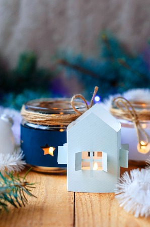 Christmas candles with Christmas tree decorations and a white candlestick house, white and blue and Christmas tree branches with a Christmas garland on a wooden table Stock Photo