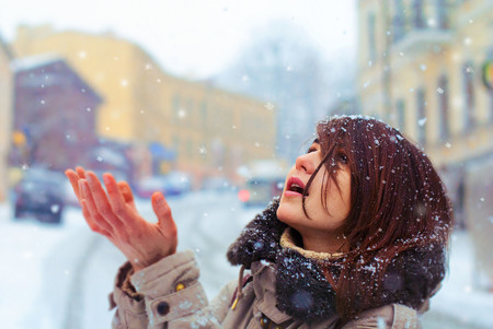 Beautiful young girl is catching snow in the winter city