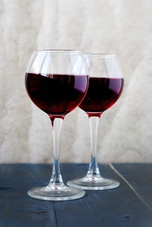 Two glass of red wine on a wooden table on a light background