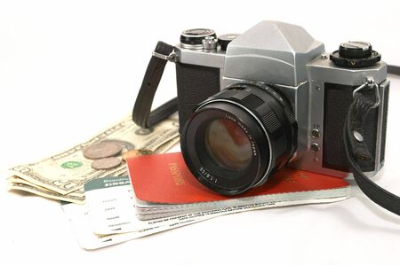 A layout of items showing old seasoned traveller, using a reliable mechanical camera, could be a photo journalist on a project, some money, passport, boarding passes Stock Photo - 414786