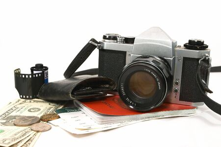 A layout of items showing old seasoned traveller, using a reliable mechanical camera, could be a photo journalist on a project, some money, passport, boarding passes, keys pouch, film cartridge photo