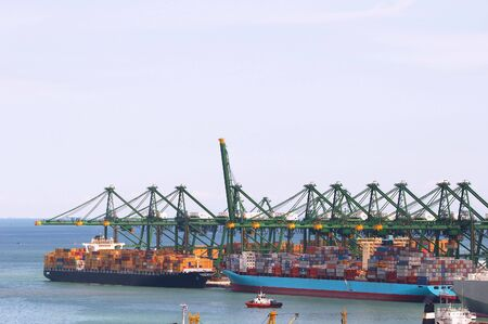 Loading of cargo onoff container ships, image can be used to show a busy port, prosperity of a harbour. photo