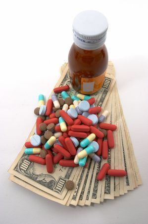 apparent: high costs of medication, bottle & pills, top view, tall perspective and apparent tall bottle emphasizes high cost. Expensive health care. Symmetrical