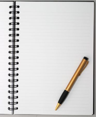 spread the word: Empty blank ring, spiral notepad, one stylish gold pen on bottom right Stock Photo