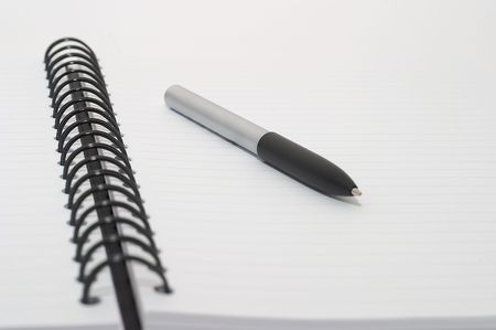 Empty blank ring, spiral notepad, pen, high key image, shallow depth of field photo