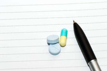 Empty blank ring, notepad, one slanted black pen on bottom right white page with pills to indicate relation with pharmaceutical industry, or metaphor for stress or work-related drug usage photo