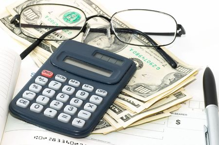 Note pad with pen, calculator, cheque book, cash and glasses. photo