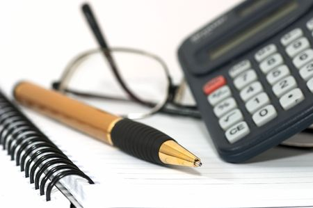 depicts: Note pad with pen, calculator, and glasses. glasss on table depicts tiredness Stock Photo