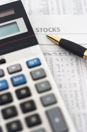 indicates: Stock market table analysis, calculator and pen indicates research and analysis, vertical orientation, pen pointing to word stocks, shallow depth of field