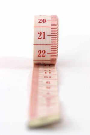De uitrol van een meetlint, geïsoleerd op witte achtergrond, ondiepe scherptediepte, met eind van tape weergegeven.