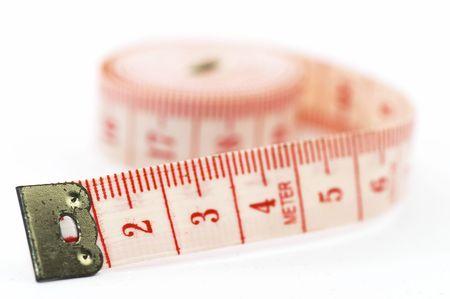 De uitrol van een meetlint, geïsoleerd op een witte achtergrond, rolde op zijn kant, met ondiepe scherptediepte. Stockfoto