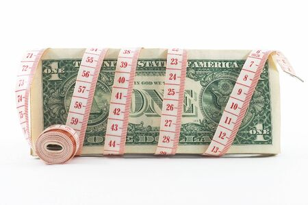 Measuring tape over money, budgeting, measure money, tight budget. Rolled tape shown. Stock Photo - 574604