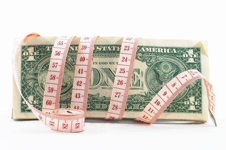 cintas metricas: La cinta que mide sobre el dinero, presupuestando, mide el dinero, presupuesto apretado. Cinta rodada en su lado. Foto de archivo