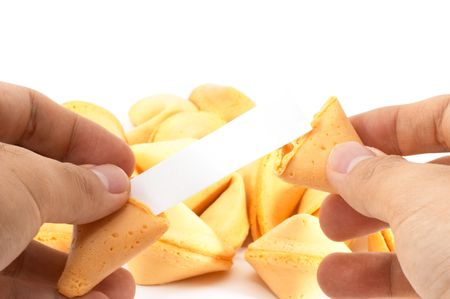 bad fortune: Pair of hands opening a fortune cookie with blank label, and a heap of cookies in the back, on white background. One-in-a-million. Stock Photo
