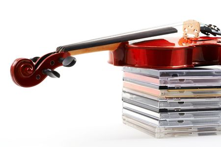 discs: Violin lying down on stack of compact discs on white background, top angle view, horizontal, landscape orientation. Depicts a career in classical music. Commercialization of classical music. Stock Photo
