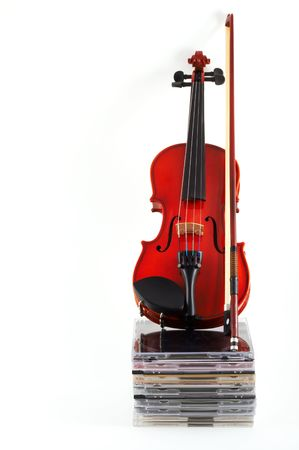 upright: Violin with bow standing upright on stack of compact discs on white background, top angle view, portrait, vertical orientation. Depicts a career in classical music. Commercialization of classical music. Stock Photo