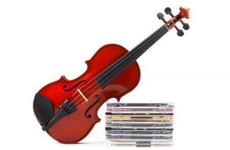 musica clasica: Viol�n apoyados en la pila de discos compactos sobre fondo blanco, �ngulo de vista superior, la orientaci�n horizontal. Presenta una carrera en la m�sica cl�sica. La comercializaci�n de la m�sica cl�sica. Foto de archivo