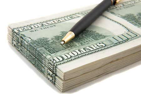 financials: Pen on top of a stack of cash, indicate agreement, deals, businesses involving cash and finances