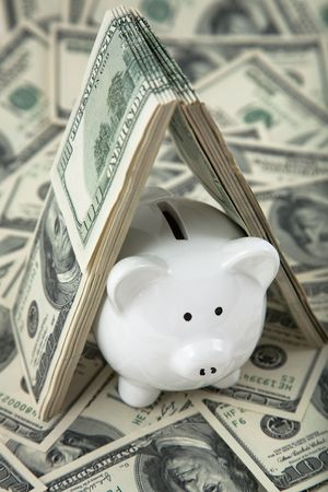 money box: Close up of a cute Piggy Bank under shelter of cash. Shallow depth of field. Stock Photo