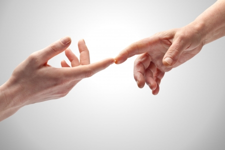 Twee vrouwelijke handen van verschillende leeftijden zachtjes aanraken met de wijsvingers