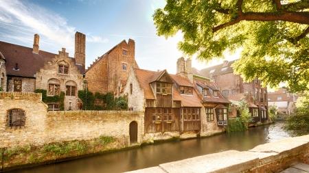 belgie: Een rij van oude huizen naast een water gracht in het historische centrum van Brugge, België
