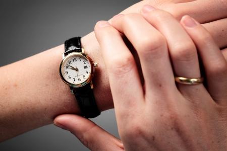 Vrouwelijke handen die de tijd op een polshorloge Stockfoto