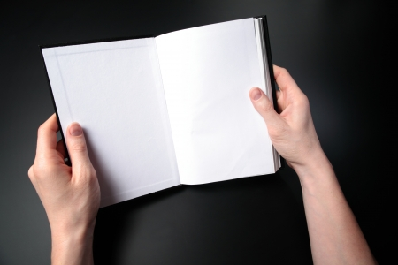 Two female hands holding a book in a reading position  Copy space on both pages
