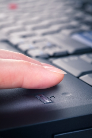 Female accessing a secure notebook with a fingerprint reader  Closeup vertical image  photo