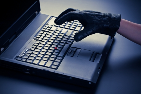 Concept image of the hand of a thief over a mobile computer or laptop  photo