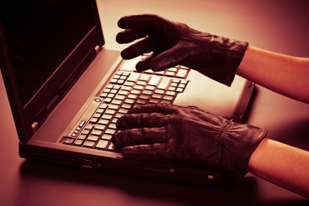 Two hands in black leather gloves stealing information from a mobile computer  Online or Internet identity theft concept  photo