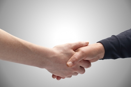 Two female hands of different ages holding each other in a handshake  Copy space on top  Stock Photo