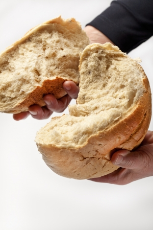 An elderly woman breaking white bread  Communion or food concept