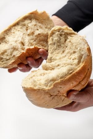 Egy idős asszony törés fehér kenyér közösség vagy az élelmiszer fogalmát Stock fotó