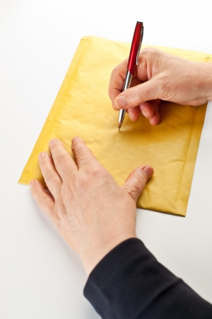 An elderly woman labeling a parcel by hand.