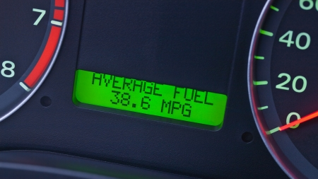 mpg: A closeup on the dashboard of a modern car with focus on the trip computer screen  Readout of the average fuel consumption