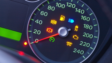 A closeup on the dashboard of a modern car with many warning lights