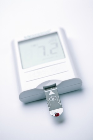 A blood sugar meter showing a value within the normal range  Photographed over a plain background  Focus on the blood sample