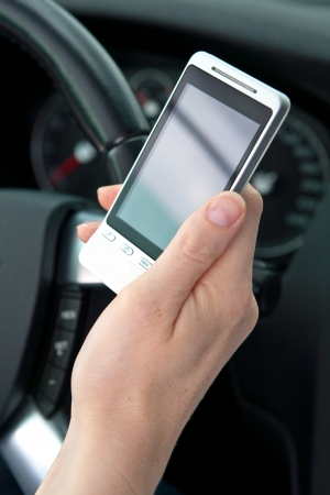 A female hand holding a phone near the steering wheel of a car photo