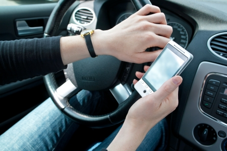 A young female driving and using a mobile phone photo