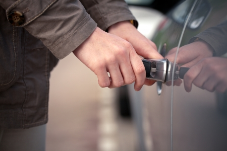 The hands of a woman unlocking a vehicle with a classic key