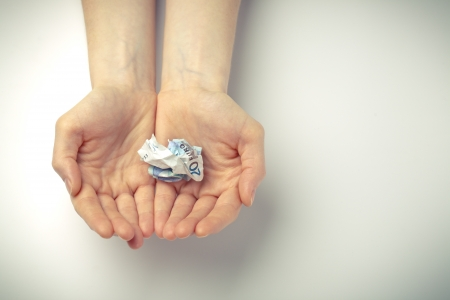 Two open hands of a woman holding a crumpled bill of 20 EUR.